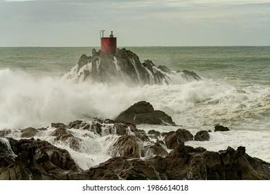 Dramatic storm waves smashing and splashing around North Rock and it's red beacon at Mount Maunganui, New Zealand.