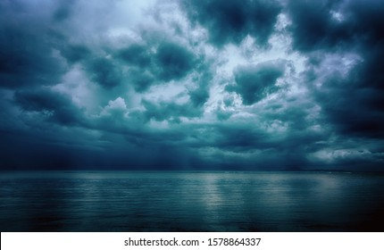 Dramatic stormy dark cloudy sky over sea, natural photo background.