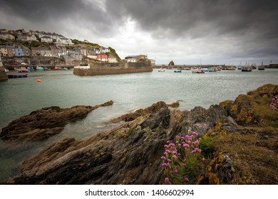 Dramatic stormy skies above a harbour scene in the quaint traditional Cornish fishing village of Mevagissey, Cornwall, England, UK
