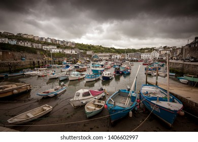 Dramatic stormy skies in a harbour scene in the quaint traditional Cornish fishing village of Mevagissey, Cornwall, England, UK