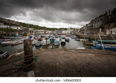 Dramatic stormy sky, harbour full of boats and yachts in the quaint traditional Cornish fishing village of Mevagissey, Cornwall, England, UK