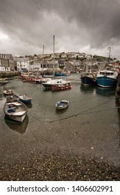 Dramatic stormy sky over a harbour full of boats and yachts in the quaint traditional Cornish fishing village of Mevagissey, Cornwall, England, UK