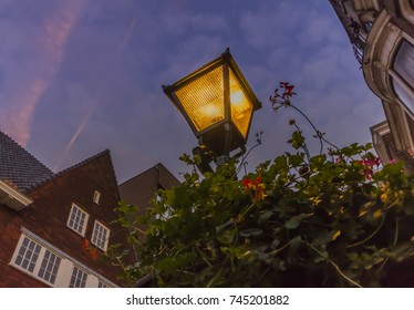 Dramatic street lights on western type of architecture on the background  with purple sky and red 5d551de99