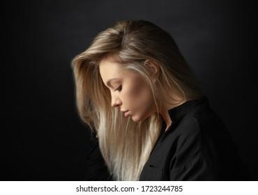 Dramatic studio portrait of beautiful young woman on dark background.