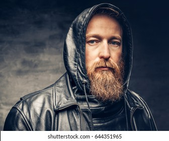Dramatic studio portrait of redhead bearded male dressed in a leather jacket over dark grey vignette background.