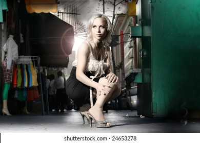 Dramatic stylized fashion portrait of female model in the city with clothing racks, mannequin and flares behind her