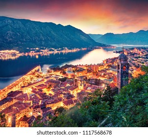 Dramatic summer sunset in Kotor port. Aerial evening view of Kotor bay and Old Town from hill of  Lovcen Mountain. Beautiful world of Mediterranean countries. Traveling concept background.