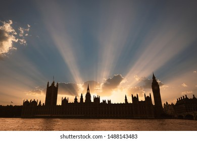 Dramatic sun beams behind the Palace of Westminster as the sun sets in London, UK.