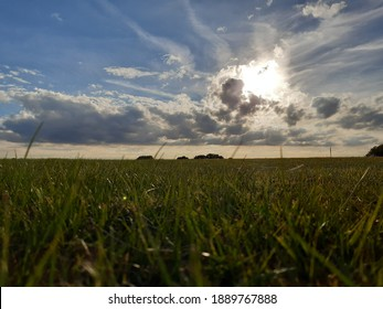 Dramatic sun rays breaking through clouds over green  grassland fields  with grass detail in English countryside,  Luton, Bedfordshire