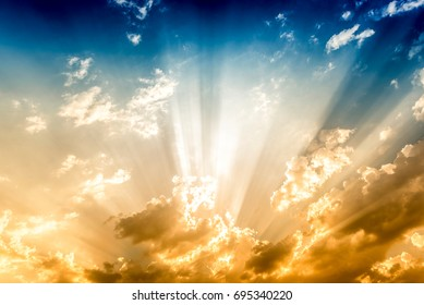 Dramatic sun rays and clouds as background