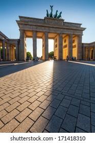 Dramatic sunlit Brandenburg Gate (1788), Berlin, Germany.