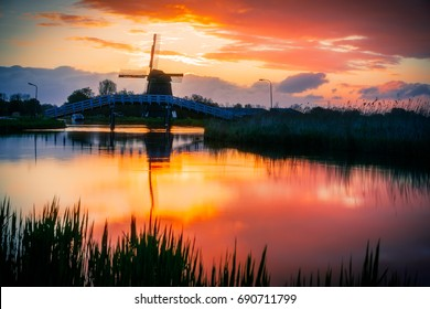 Dramatic sunrise colors in Friesland, Holland, with a traditional windmill profiling on the cloudy sky