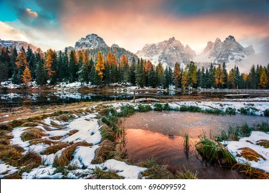 Dramatic sunrise on Antorno lake. Picturesque autumn morning in Dolomite Alps, Province of Belluno, Italy, Europe. Beauty of nature concept background.