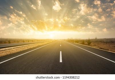 dramatic sunrise on asphalt road