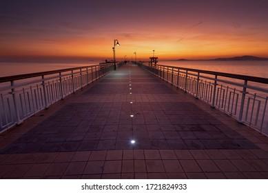 Dramatischer Sonnenaufgang am Strand in Burgas, Bulgarien. Sonnenaufgang auf der Burgas-Brücke. Brücke in Burgas - Symbol der Stadt.