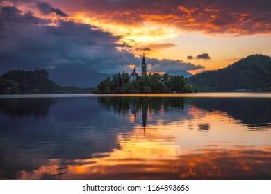 Dramatic sunrise on lake Bled, sunrise view on Bled lake, island, Pilgrimage Church of the Assumption of Maria and Castle with mountain range (Stol, Vrtaca, Begunjscica). Bled, Slovenia,