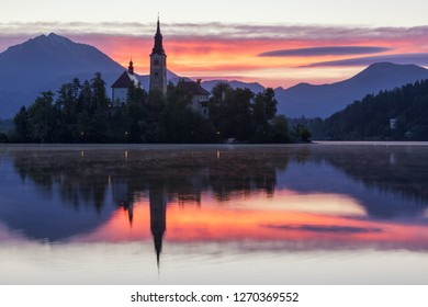 Dramatic sunrise on lake Bled, sunrise view on Bled lake, island, Pilgrimage Church of the Assumption of Maria and Castle with mountain range (Stol, Vrtaca, Begunjscica). Bled, Slovenia,