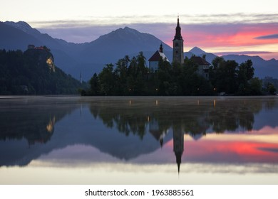 Dramatic sunrise on lake Bled, sunrise view on Bled lake, island, Pilgrimage Church of the Assumption of Maria and Castle with mountain range (Stol, Vrtaca, Begunjscica). Bled, Slovenia, - Shutterstock ID 1963885561
