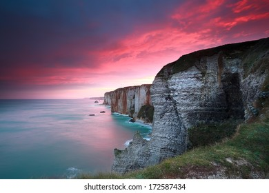dramatic sunrise over cliffs in Atlantic ocean, Etretat, France