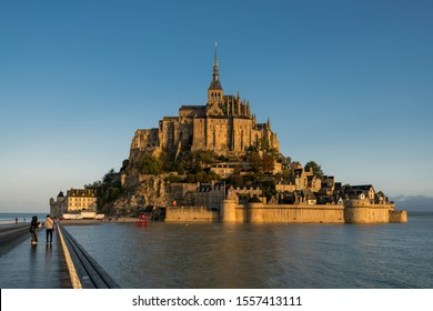 Dramatic sunrise over the famous Mont Saint-Michel, a town located in Normandy west of Paris on the small island near the riverside. Amazing view of French old Gothic architecture.