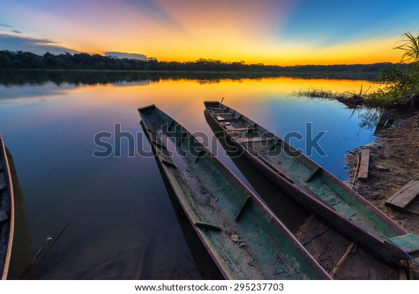Dramatic sunset in the Amazon rain forest in Bolivia in Madidi National Park with two canoes in the foreground