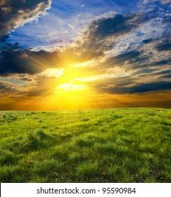 dramatic sunset among a green fields
