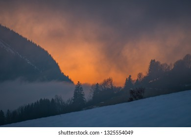 Dramatic sunset behind the forest near mountain Grimming on a very foggy evening on a winterday in Styria, Austria