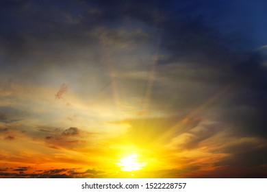 Dramatic sunset with bright rays and dark clouds in sky.