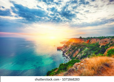 Dramatic sunset at cape Fiolent with bushes grass and rocks at foreground. Crimea