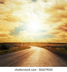 dramatic sunset in clouds over asphalt road
