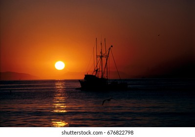 A dramatic sunset as a commercial fishing boat returns to port.