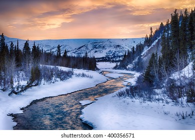 A dramatic sunset illuminates the clear waters of Phelan Creek in early spring in the Alaska Range