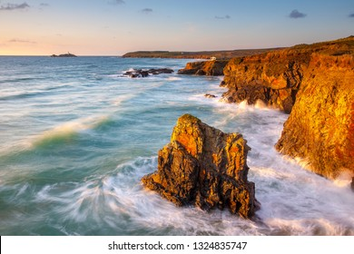 Dramatic sunset light illuminating the cliffs at Gwithian Cornwall England UK with Godrevy Island on the Horizon.