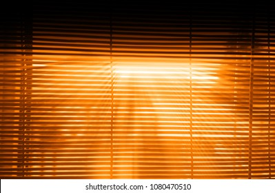 Dramatic sunset light rays through jalousie interior backdrop
