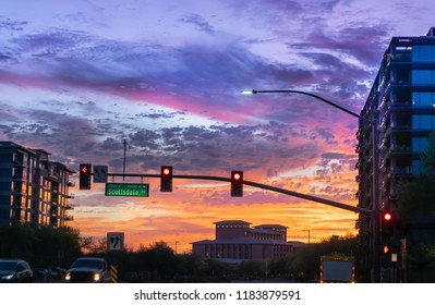 Dramatic sunset in North  Scottsdale,Arizona.  Cars drive by a busy intersection on Scottsdale rd and Kierland Blvd. Focus on road sign.