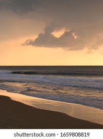 Dramatic sunset on the beach with clouds, breaking waves and golden colors