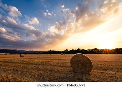 Dramatic sunset on a field of Straw after the harvest, with bales of Straw in the foreground
