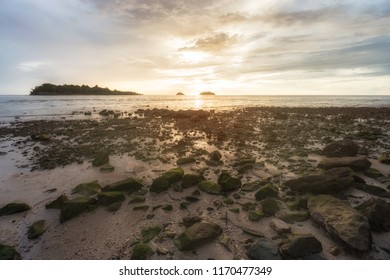 Dramatic sunset on a tropical dessert island beach full of rocks in Asia