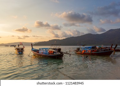Dramatic sunset over Beach at Lipe Island, Thailand, with traditional longtail boat in the foreground.