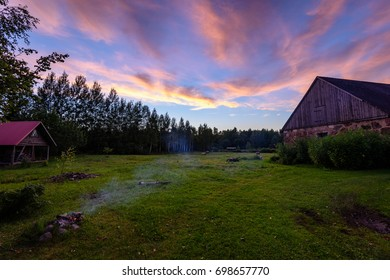 dramatic sunset over countryside in summer with house and fire place