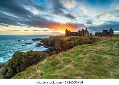 Dramatic sunset over the eerie ruins Slains Castle near Peterhead on the east coast of Scotland