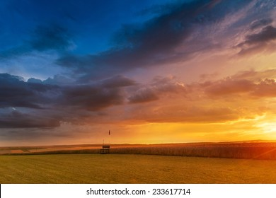 Dramatic sunset over fields with clouds during late summer