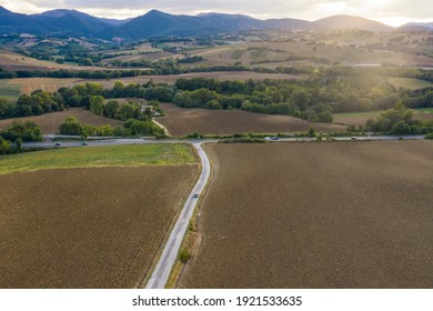 Dramatic sunset over the hills in Fabriano, Marche region, Italy. Aerial shot, country road wuth an isolated tree
