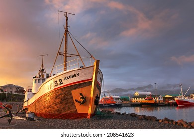Dramatic sunset over the Hofn harbor in south-eastern part of Iceland. The composition focuses on the shipwreck of an old fishing boat, nowadays decorating the harbor.