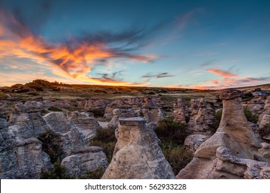 Dramatic sunset over the Hoodoo badlands at Writing on Stone Provincial Park and Aisinaipi National Historic Site in Alberta, Canada. The area contains many First Nation petroglyphs and pictographs.