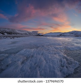Dramatic sunset over the icy lake in the Arctic tundra. Yamal peninsula.
