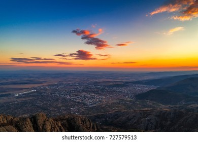 Dramatic sunset over the mountain hills and Sliven city, aerial panoramic view