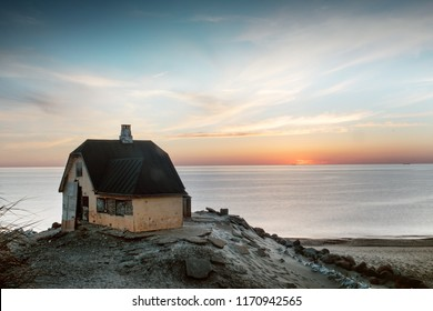 Dramatic sunset over the north sea with a house direct on the beach overlooking the sea. Coastline of Skagen, Top of Denmark in North Jutland in Denmark, Skagerrak, North Sea