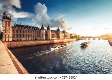 Dramatic sunset over river Seine and Conciergerie in Paris, France, with cruise boats and Pont Neuf. Colourful travel background. Romantic cityscape.