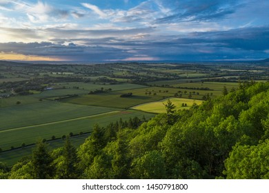 Dramatic sunset over scenic farming fields. Drone shoot over trees in Much Wenlock Edge in Shropshire, UK
